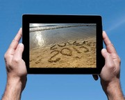 Hands holding iPad with beach scene, 2012 & 2013 written in sand, wave is washing 2012 away